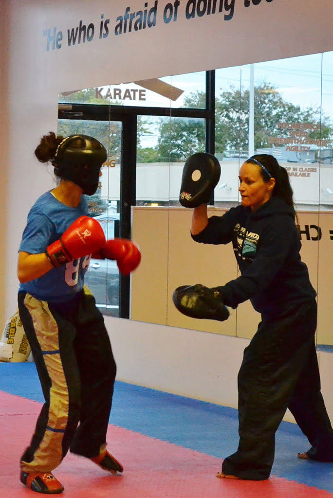 Tammy Bernardo holding mits for a student as they punch