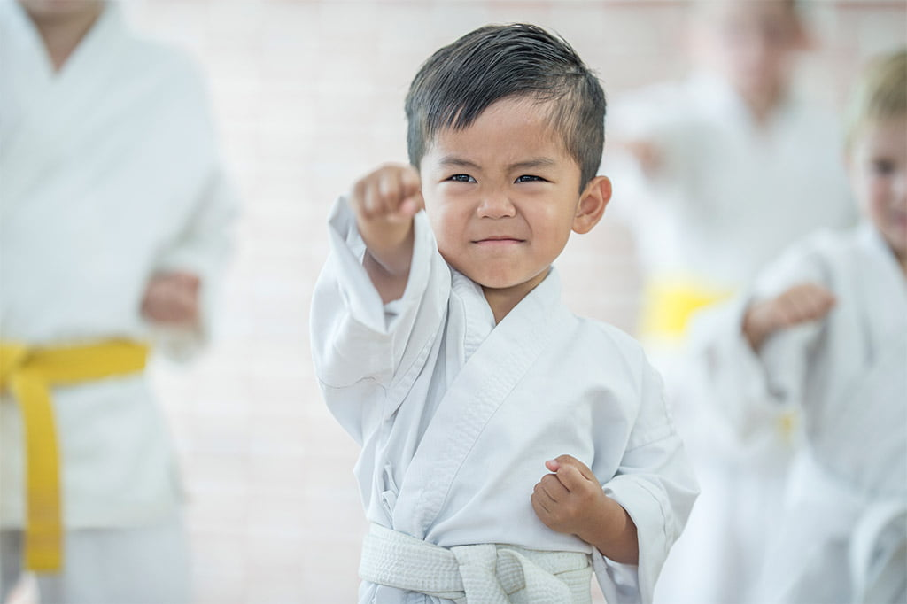 young boy punching forward wearing white belt